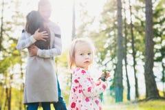 Счастливая молодая семья принимая прогулку в парке Дочь девушки малыша смотря камеру на переднем плане Стоковые Фотографии RF