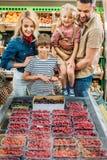 счастливая молодая семья при 2 дет выбирая ягоды Стоковые Фотографии RF