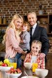 счастливая молодая семья при 2 дет усмехаясь на камере пока имеющ завтрак Стоковая Фотография RF