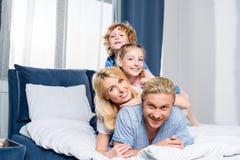 счастливая молодая семья при 2 дет усмехаясь на камере пока лежащ совместно Стоковая Фотография RF