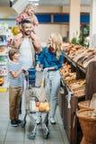 счастливая молодая семья при 2 дет ходя по магазинам совместно Стоковые Изображения RF
