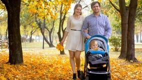 Счастливая молодая семья при 1-ти летний ребёнок идя в красивый парк осени Стоковое Фото