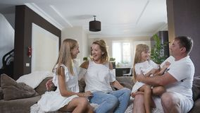 Счастливая молодая семья сидя на софе в живущей комнате дома Счастливая семья тратя время совместно дома папа видеоматериал