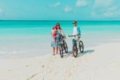 Счастливая молодая семья с велосипедами младенца ехать на пляже стоковая фотография rf