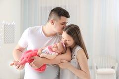 Счастливая молодая семья с милым спать newborn младенцем стоковая фотография