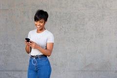 Счастливая молодая чернокожая женщина смотря мобильный телефон и слушая к музыке Стоковое фото RF