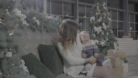 Счастливая молодая excited мать женщины играя с ее младенцем мальчика в рождественской елке украсила праздничную уютную комнату с сток-видео