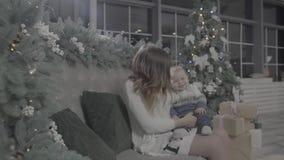 Счастливая молодая excited мать женщины играя с ее ребёнком в рождественской елке украсила праздничную уютную комнату студии сток-видео