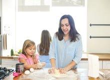 Счастливая молодые мать и дочери лить муку через сетку для стоковые изображения rf