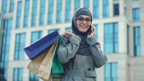 Счастливая мусульманская дама беседуя на торговом центре outdoors телефона, черной продаже пятницы видеоматериал