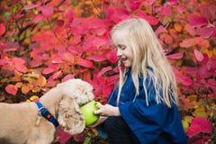 Счастливая небольшая девушка с spaniel кокерспаниеля outdoors стоковое фото rf