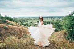 Счастливая невеста бежит в платье свадьбы, против фона красивой природы Стоковые Фотографии RF