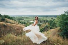 Счастливая невеста бежит в платье свадьбы, против фона красивой природы Стоковые Изображения