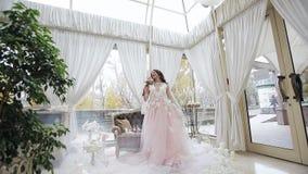 Счастливая невеста в платье свадьбы завихряется в танце с ее букетом свадьбы Маленькая девочка в красивом розовом платье видеоматериал