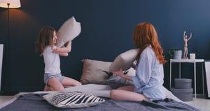 Счастливая няня мамы семьи и дочь маленького ребенка имея бой подушками на кровати, игру потехи молодой няни матери смеясь сток-видео