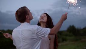 Счастливая пара в влюбленности горит света Бенгалии outdoors Парень и девушка целуют видеоматериал