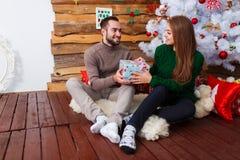 Счастливая пара давая подарки рождества одина другого сидя под деревом indoors стоковое изображение rf