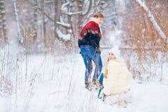 Счастливая пара едет скелетон в снеге в парке в выигрыше Стоковые Изображения RF