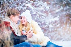 Счастливая пара едет скелетон в снеге в парке в выигрыше Стоковые Фото