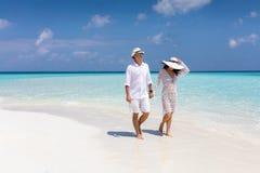 Счастливая пара идет вниз с тропического пляжа стоковая фотография