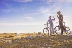 Счастливая пара идет на дорогу асфальта горы в древесинах на велосипедах при шлемы давая одину другого высокие 5 Стоковое Изображение
