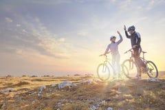 Счастливая пара идет на дорогу асфальта горы в древесинах на велосипедах при шлемы давая одину другого высокие 5 Стоковые Фото