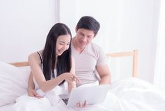 Счастливая пара использует компьтер-книжку на кровати утра с улыбкой Стоковое Фото