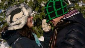 Счастливая пара любовников идет до покрытый снег лес они стоят около дерева и нежно смотрят один другого сток-видео