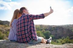 Счастливая пара молодых туристов делает фото selfie в природе Отключение лета с полюбленное одним Selfie горы в лете Стоковые Фотографии RF