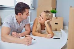 Счастливая пара рисует план на поле в новой квартире Стоковое Изображение