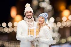 Счастливая пара с подарком рождества над ночой освещает Стоковые Изображения RF