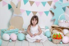 Счастливая пасха! Красивая маленькая девочка в белом платье с пасхальными яйцами и корзина около ярких украшений Зайчик пасхи и c стоковая фотография