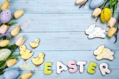 Счастливая пасха красочная помечая буквами пасха зайчика печениь и печений имбиря на деревянной голубой предпосылке Стоковая Фотография RF