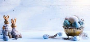 Счастливая пасха; Пасхальные яйца и зайчик пасхи на голубом backgr таблицы Стоковые Фотографии RF
