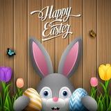 Счастливая пасха при кролик держа яичко 2 красочный на деревянной серой предпосылке бесплатная иллюстрация