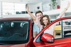 Счастливая подруга стоя с ключом и руками автомобиля вверх, парень стоковое фото rf