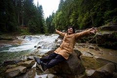 Счастливая пожилая женщина наслаждаясь природой около потока горы Стоковая Фотография RF