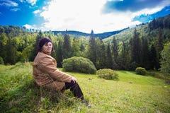 Счастливая пожилая женщина сидя na górze холма в горе Стоковые Фото