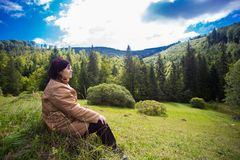Счастливая пожилая женщина сидя na górze холма в горе Стоковое Изображение