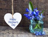 Счастливая поздравительная открытка дня ` s матери с декоративным белым сердцем и голубой весной цветет в стеклянной вазе на стар стоковые изображения rf