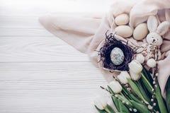 Счастливая поздравительная открытка пасхи стильные пасхальные яйца в гнезде с плюшкой Стоковое Изображение RF