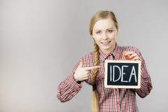 Счастливая положительная женщина держа знак идеи Стоковое фото RF