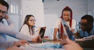 Счастливая положительная черная молодая бизнес-леди сотрудничая с многонациональными коллегами на современной ультрамодной встреч сток-видео