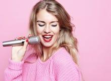 Счастливая поя девушка Женщина красоты нося розовый пуловер с mic Стоковые Фото