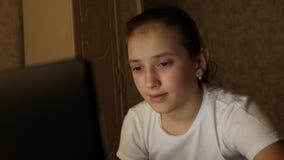 Счастливая предназначенная для подростков девушка играя игры на ноутбуке Маленькая девочка смотрит экран и улыбки компьютера в ее сток-видео