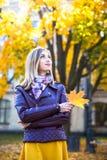 Счастливая предназначенная для подростков девушка с желтой улыбкой лист во время идти на парк осени Концепция падения Стоковая Фотография