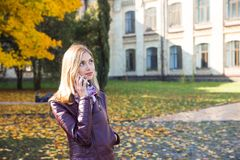 Счастливая предназначенная для подростков девушка с улыбкой телефона во время идти на парк осени Концепция падения Стоковое Фото