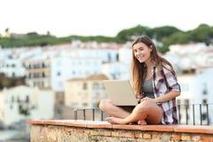 Счастливая предназначенная для подростков смотря камера используя ноутбук стоковое изображение