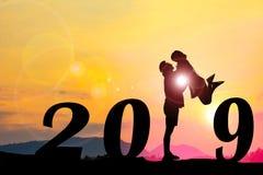 Счастливая предпосылка захода солнца силуэта Нового Года Женщина положения и подъема человека стоковые фотографии rf