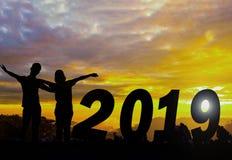 Счастливая предпосылка захода солнца силуэта Нового Года Они стоят около слова 2019 и видят набор солнца стоковая фотография